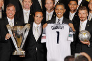 """U.S. President Barack Obama (2nd R) poses for photographs with the Major League Soccer champions Los Angeles Galaxy, including General Manager and Head Coach Bruce Arena (L) and mid-fielders Landon Donovan and David Beckham (R) in the East Room of the White House May 15, 2012 in Washington, DC. Players from the Galaxy also participated in a """"Let's Move!"""" question and answer session with school-age sports fans and first lady Michelle Obama after the ceremony."""
