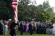U.S. President Barack Obama, first lady Michelle Obama, Vice President Joseph Biden, his wife Jill Biden, and White House staff listen to 'Taps' as they observe a moment of silence to mark the 12th anniversary of the 9/11 attacks September 11, 2013 on the South Lawn of the White House in Washington, DC. The nation is commemorating the anniversary of the 2001 attacks which resulted in the deaths of nearly 3,000 people after two hijacked planes crashed into the World Trade Center, one into the Pentagon in Arlington, Virginia and one crash landed in Shanksville, Pennsylvania.