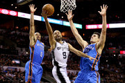 Tony Parker #9 of the San Antonio Spurs goes up for a shot between Russell Westbrook #0 and Steven Adams #12 of the Oklahoma City Thunder in the first half in Game One of the Western Conference Finals during the 2014 NBA Playoffs at AT&T Center on May 19, 2014 in San Antonio, Texas. NOTE TO USER: User expressly acknowledges and agrees that, by downloading and or using this photograph, User is consenting to the terms and conditions of the Getty Images License Agreement.