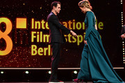 Host Anke Engelke (R) and Jury President Tom Tykwer are seen on stage at the Opening Ceremony & 'Isle of Dogs' premiere during the 68th Berlinale International Film Festival Berlin at Berlinale Palace on February 15, 2018 in Berlin, Germany.