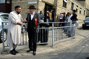 The Respect Party's George Galloway (2ndL) speaks to a man outside Masjid Noorul Islam mosque during his election campaigning on April 24, 2015 in Bradford, England. Britain goes to the polls in a General Election on May 7.