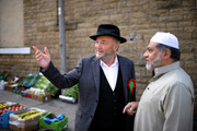 The Respect Party's George Galloway (L) speaks to a man during his election campaigning on April 24, 2015 in Bradford, England. Britain goes to the polls in a General Election on May 7.