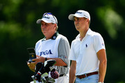 Justin Thomas of the United States stands with caddie Jimmy Johnson on the first hole during the first round of the 2018 PGA Championship at Bellerive Country Club on August 9, 2018 in St Louis, Missouri.