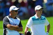 Justin Rose of England and caddie Mark Fulcher ponder on the first hole during the third round of the 95th PGA Championship on August 10, 2013 in Rochester, New York.