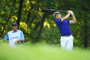 Justin Thomas of the United States plays his shot from the 11th tee as his caddie Jimmy Johnson looks on during the continuation of the weather delayed second round of the 2018 PGA Championship at Bellerive Country Club on August 11, 2018 in St Louis, Missouri.