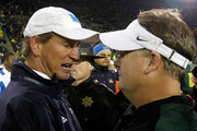 Head coach Chip Kelly of the Oregon Ducks shakes hands with head coach Rick Neuheisel of the UCLA Bruins  after the 49-31 victory during the Pac 12 Championship Game on December 2, 2011 at the Autzen Stadium in Eugene, Oregon.