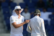 England captain Alastair Cook taps Shoaib Malik of Pakistan on the back as he leaves the field after being dismissed by Ben Stokes during day two of the 1st Test between Pakistan and England at Zayed Cricket Stadium on October 14, 2015 in Abu Dhabi, United Arab Emirates.