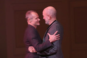 Flea and Michael Stipe embrace on stage during Pathway To Paris Concert For Climate Action at Carnegie Hall on November 5, 2017 in New York City.