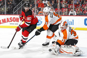 Brian Elliott #37 of the Philadelphia Flyers makes a save in front of Marcus Johansson #90 of the New Jersey Devils during the second period at the Prudential Center on January 13, 2018 in Newark, New Jersey.