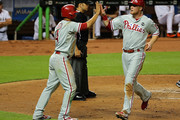 Cody Asche #25 of the Philadelphia Phillies is congratulated by Andres Blanco #4 after scoring a run during a game against the Miami Marlins at Marlins Park on September 22, 2015 in Miami, Florida.