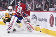 Goaltender Antti Niemi #37 of the Montreal Canadiens tries to clear the puck with Evgeni Malkin #71 of the Pittsburgh Penguins challenging from behind during the NHL game at the Bell Centre on October 13, 2018 in Montreal, Quebec, Canada.
