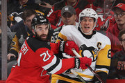 Kyle Palmieri #21 of the New Jersey Devils checks Sidney Crosby #87 of the Pittsburgh Penguins into the boards during the first period at the Prudential Center on February 19, 2019 in Newark, New Jersey.