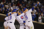 (L-R) David Bote #13, Ben Zobrist #18, Anthony Rizzo #44 and Javier Baez #9 of the Chicago Cubs pretend to take a selfie after a win over the Pittsburgh Pirates at Wrigley Field on September 27, 2018 in Chicago, Illinois. The Cubs defeated the Pirates 3-0.