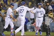 Matt Kemp #27 of the Los Angeles Dodgers is congratulated for his 3 run home run by Logan Forsythe #11 and Max Muncy #13 as Jacob Stallings #58 of the Pittsburgh Pirates looks on at the plate in the sixth inning at Dodger Stadium on July 2, 2018 in Los Angeles, California.