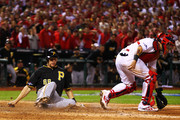 Justin Morneau #66 of the Pittsburgh Pirates slides into home to score on a single by Pedro Alvarez #24 in the seventh inning against the St. Louis Cardinals during Game Five of the National League Division Series at Busch Stadium on October 9, 2013 in St Louis, Missouri.