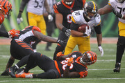 James Conner #30 of the Pittsburgh Steelers slips past Vontaze Burfict #55 and Shawn Williams #36 of the Cincinnati Bengals during the third quarter at Paul Brown Stadium on October 14, 2018 in Cincinnati, Ohio.