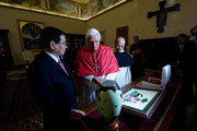 Pope Benedict XVI exchanges gifts with Vietnamese President Nguyen Minh Triet during their meeting at his library on December 11, 2009 in Vatican City, Italy.