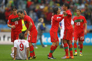 Pedro Mendes and Bruno Alves of Portugal celebrate victory (R) as Ricardo Carvalho (L) consoles Jong Tae-Se of North Korea during the 2010 FIFA World Cup South Africa Group G match between Portugal and North Korea at the Green Point Stadium on June 21, 2010 in Cape Town, South Africa.