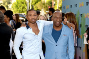 """Actor Malcolm Mays (L) and John Singleton arrive at the premiere of FX's """"Snowfall"""" Season 2 at the Regal Cinemas L.A. LIVE Stadium 14 on July 16, 2018 in Los Angeles, California."""