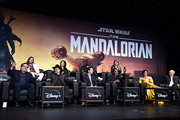 "(L-R) Executive Producer Jon Favreau, Composer Ludwig Göransson, Executive Producer/Director Dave Filoni, Director Deborah Chow, Pedro Pascal, Rick Famuyiwa, Carl Weathers, Director Bryce Dallas Howard, Gina Carano and Werner Herzog speak onstage at the premiere of Lucasfilm's first-ever, live-action series, ""The Mandalorian,"" at the El Capitan Theatre in Hollywood, Calif. on November 13, 2019. ""The Mandalorian"" streams exclusively on Disney+."