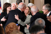 Vice President Joseph Biden hugs Speaker of the House Rep. Nancy Pelosi (D-CA) (C) as widow of the late Sen. Edward Kennedy (D-MA) Vicki Kennedy (L), and Senate Majority Leader Sen. Harry Reid (D-NV) (R) look on after he signed the Affordable Health Care for America Act during a ceremony with fellow Democrats as, clockwise from left, and health care activist Marcelas Owens look on in the East Room of the White House March 23, 2010 in Washington, DC. The historic bill was passed by the House of Representatives Sunday after a 14-month-long political battle that left the legislation without a single Republican vote.