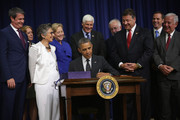 U.S. President Barack Obama signs H.R. 3080, the Water Resources Reform & Development Act of 2014 into law as (L-R) Senator David Vitter (R-LA), Jo Ellen Darcy, Assistant Secretary of the Army or John McHugh, Secretary of the Army, Senator Barbara Boxer (D-CA), Senator Mary Landrieu (D-LA), Representative Bob Gibbs (R-OH), Representative Tim Bishop (D-NY), Representative Bill Shuster (R-PA), Michael Boots, Acting Chair, Council on Environmental Quality, Representative Nick Rahall (D-WV) look on June 10, 2014 at the South Court Auditorium of the Eisenhower Executive Office Building in Washington, DC. President Obama also signed H.R. 1726 to award a Congressional Gold Medal to the 65th Infantry Regiment, known as the Borinqueneers, during the same event.