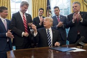 US President Donald Trump hands his pen to Representative Bill Huizenga (2nd L), Republican of Michigan, after signing House Joint Resolution 41, which removes some Dodd-Frank regulations on oil and gas companies, during a bill signing ceremony in the Oval Office of the White House in Washington, DC, February 14, 2017. / AFP / SAUL LOEB