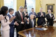 "(AFP-OUT) U.S. President Donald Trump gives the pen to Rep. Bill Huizenga (R-MI) after signing H.J. Res. 41 in the Oval Office of the White House on February 14, 2017 in Washington, DC. The resolution nullifies a rule in the Dodd-Frank Act that ""requires resource extraction issuers to disclose payments made to governments for the commercial development of oil, natural gas, or minerals."" Also pictured are House Speaker Paul Ryan (R-WI) (4th L) and Rep. Peter King (R-NY) (2nd R)."