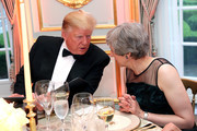 US President Donald Trump and British Prime Minister Theresa May speak at a dinner hosted by himself and First Lady Melania Trump at Winfield House for Prince Charles, Prince of Wales and Camilla, Duchess of Cornwall, during their state visit on June 04, 2019 in London, England. President Trump's three-day state visit began with lunch with the Queen, followed by a State Banquet at Buckingham Palace, whilst today he attended business meetings with the Prime Minister and the Duke of York, before traveling to Portsmouth to mark the 75th anniversary of the D-Day landings.