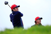 Keegan Bradley of the United States tees off as Phil Mickelson of the United States looks on during practice ahead of the 2014 Ryder Cup on the PGA Centenary course at the Gleneagles Hotel on September 25, 2014 in Auchterarder, Scotland.
