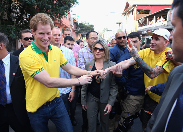 Prince Harry walks down the street after visiting the ACER Charity for disadvantaged children on June 25, 2014 in Sao Paulo Brazil.  Prince Harry is on a four day tour of Brazil that will be followed by Two days in Chile.
