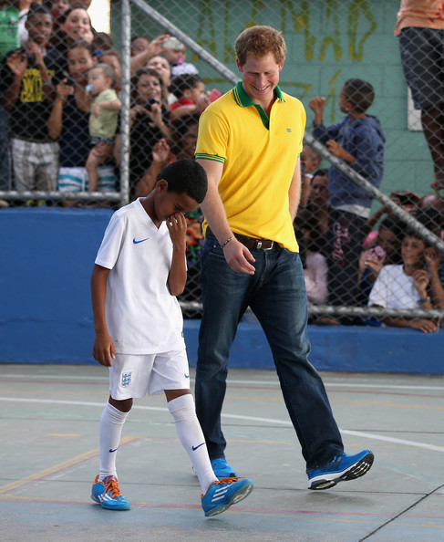 Prince Harry plays football as he visits the ACER Charity for disadvantaged children on June 25, 2014 in Sao Paulo Brazil.  Prince Harry is on a four day tour of Brazil that will be followed by Two days in Chile.