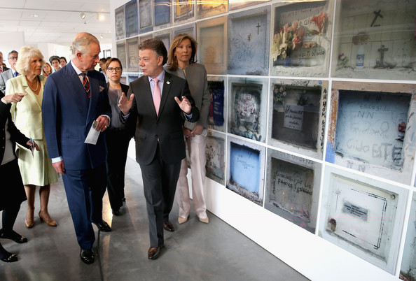 Camilla, Duchess of Cornwall poses with Prince Charles, Prince of Wales the First Lady of Colombia María Clemencia Rodríguez Múnera and the President of Colombia Juan Manuel Santos walk past images of the graves of the victims of the conflict as they visit the Centre for Peace and Reconciliation on October 30, 2014 in Bogota, Colombia. The Royal Couple are on a four day visit to Colombia as part of a Royal tour to Colombia and Mexico. After fifty years of armed conflict in Colombia the theme for the visit is Peace and Reconciliation.