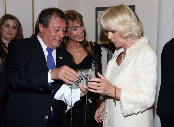 Camilla, Duchess of Cornwall is presented with a handbag by Colombian designer Mario Hernandez during a reception at the Ambassador's Residence on October 28, 2014 in Bogota, Colombia. The Royal Couple are on a four day visit to Colombia as part of a Royal tour to Colombia and Mexico. After fifty years of armed conflict in Colombia the theme for the visit is Peace and Reconciliation.