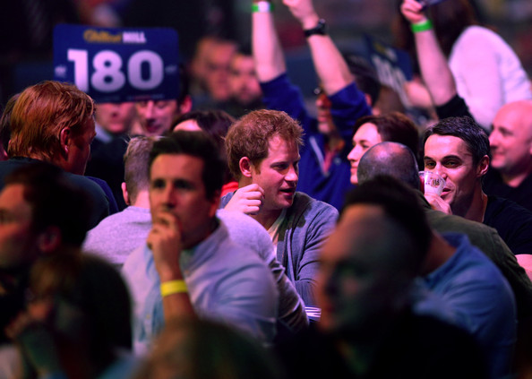 Prince Harry Prince Harry enjoys the darts match between Stephen Bunting of England and James Wade of England with friends during the William Hill PDC World Darts Championships on Day Nine at Alexandra Palace on December 29, 2014 in London, England.