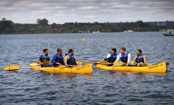Prince Harry canoes with patient Israel Lima (front R) and an instructor from the Rede Sarah Hospital for Nerological Rehabilitation injuries as he takes part in a canoe therapy session on Lake Paranoa on June 23, 2014 in Brasilia, Brazil.  Prince Harry is on a four day tour in Brazil that will be followed by two days in Chile.