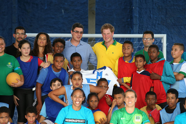 Prince Harry poses for a team picture after playing football as he visits the ACER Charity for disadvantaged children on June 25, 2014 in Sao Paulo Brazil.  Prince Harry is on a four day tour of Brazil that will be followed by Two days in Chile.