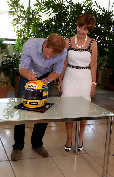 Prince Harry signs a replica Ayrton Senna helmet accompanied by Ayrton Senna's sister, Vivienne Senna, at the Ayrton Senna Institue on June 26, 2014 in Sao Paulo Brazil. Prince Harry is on a four day tour of Brazil that will be followed by two days in Chile.