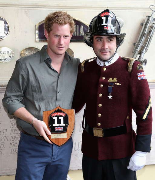 Prince Harry poses next to Fireman Gonzalo Alvarez at Valpariso Firestation on June 28, 2014 in Valpariso, Chile. Firefighters from Valpariso were involved in dealing with the devastating forest fires that hit the area in April. Prince Harry is on a three day tour of Chile after visiting Brazil.