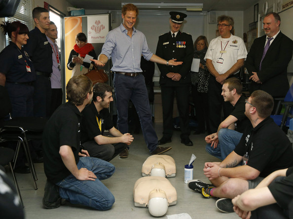 Prince Harry gestures as he chats with Prince's Trust volunteers during a first aid lesson during his visit to Salford Fire Station on October 20, 2014 in Manchester, England.