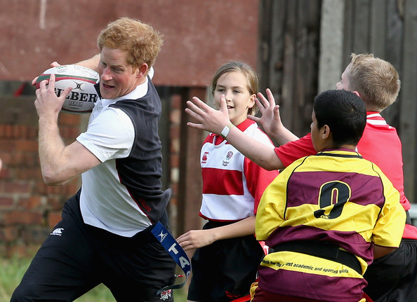 Prince Harry, Patron of England Rugby's All Schools Programme, plays touch rugby against schoolchildren during a teacher training session at Eccles RFC on October 20, 2014 in Manchester, England.