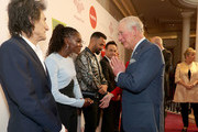 Prince Charles, Prince of Wales uses the Namaste gesture to greet Dina Asher-Smith as he attends the Prince's Trust And TK Maxx & Homesense Awards at London Palladium on March 11, 2020 in London, England.