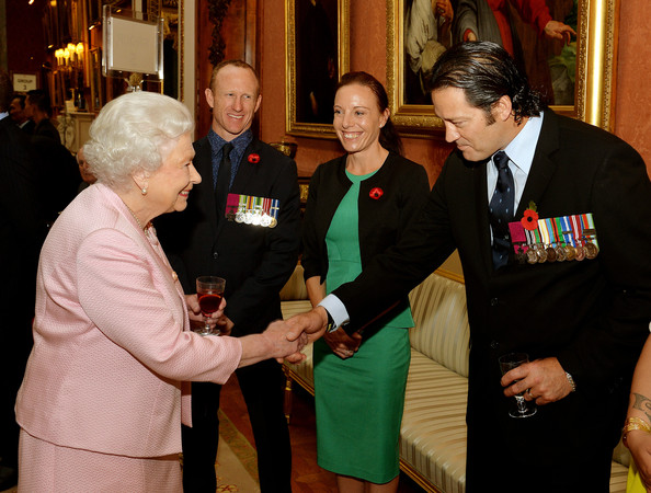 Queen Elizabeth II smiles as she talks to Corporal Mark Donaldson VC of the Australian Special Air Service, his wife Emma (centre) and Corporal Willie Apiata VC (right) of the New Zealand Special Air Service, at a reunion reception for the Victoria and George Cross Association, in the picture Gallery of Buckingham Palace on October 28, 2014 in central London.