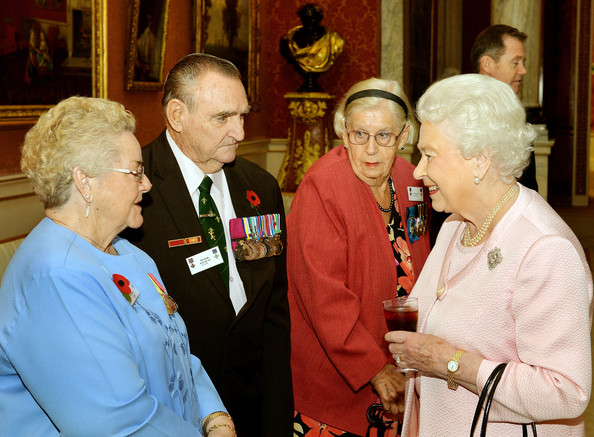 Queen Elizabeth II smiles as she talks to (left - right) Florence Payne, her husband Derek VC, and Margaret Purves GC at a reunion reception for the Victoria and George Cross Association, in the picture Gallery of Buckingham Palace on October 28, 2014 in central London.