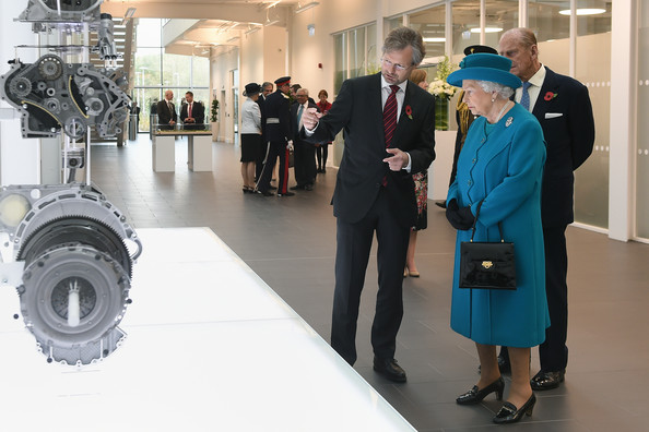 Queen Elizabeth II and Prince Philip, Duke of Edinburgh are shown an exploded engine by director of manufacturing Wolfgang Stadler at the new Jaguar Land Rover Engine Manufacturing Centre in Wolverhampton on October 30, 2014 in Wolverhampton.