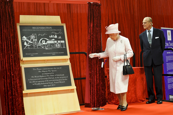 Prince Philip, Duke of Edinburgh looks on as Queen Elizabeth II unveils a plaque during a visit to International Greetings UK Ltd at the Penallta Industrial Estate in Ystrad Mynach during her visit to south west Wales on April 30, 2014 in Ystrad Mynach, Wales.