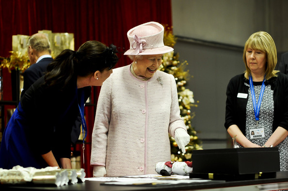 Queen Elizabeth II is shown how her Christmas crackers are made during a visit to International Greetings UK Ltd at the Penallta Industrial Estate in Ystrad Mynach during her visit to south west Wales on April 30, 2014 in Ystrad Mynach, Wales.