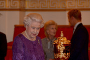 Queen Elizabeth II looks at the Webb Ellis Cup on a plinth during a reception to mark the Rugby World Cup 2015 at Buckingham Palace on October 12, 2015 in London, United Kingdom.