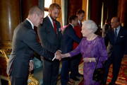 Queen Elizabeth II shakes hands with England Rugby Union head coach Stuart Lancaster (left) as England captain Chris Robshaw (second left) looks on, during a reception to mark the Rugby World Cup 2015 at Buckingham Palace on October 12, 2015 in London, United Kingdom.