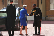 Prime Minister Theresa May is greeted by Major Nana Twumasi-Ankrah, Household Cavalry Regiment as she arrives at Buckingham Palace on July 24, 2019 in London, England. The British monarch remains politically neutral and the incoming Prime Minister visits the Palace to satisfy the Queen that they can form her government by being able to command a majority, holding the greater number of seats, in Parliament.  Then the Court Circular records that a new Prime Minister has been appointed.
